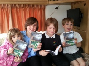 My children posing with my novel